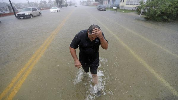 Parts of eastern Texas could see nearly 3 feet of rain through Friday, forecasters say, warning of potential flash floods from Tropical Depression Imelda. Here, Angel Marshman walks through floodwaters in Galveston after trying to start his flooded car Wednesday.