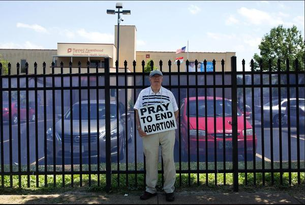 A volunteer with Coalition for Life St. Louis protests outside the Planned Parenthood clinic.