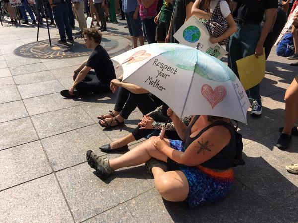 One rally attendee put her messages not on a sign, but on the umbrella she was using to beat the heat.