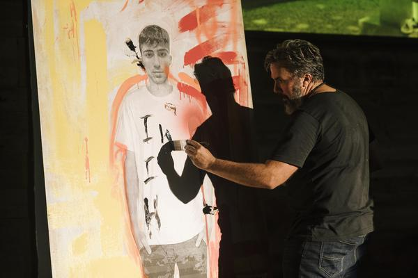 """Manuel Oliver, father of Joaquin Oliver who died in Parkland, paints on stage during his one-man show """"GUAC: My Son, My Hero,"""" which tells the story of his son."""