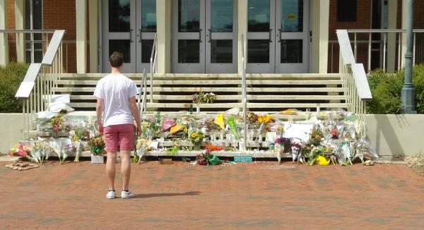 A student contemplates a shrine of flowers left outside Kennedy Hall at UNC Charlotte after a mass shooting in a classroom in April killed two students and wounded four others.