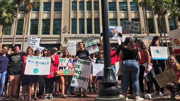About 100 people participate in a climate strike outside of Jacksonville's City Hall on Friday.