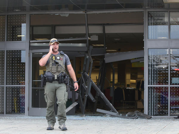 A state police officer stands outside a Woodfield Mall entrance on Friday, in Schaumburg, Ill. An SUV drove into the mall through the Sears entrance and crashed into several stores and kiosks.