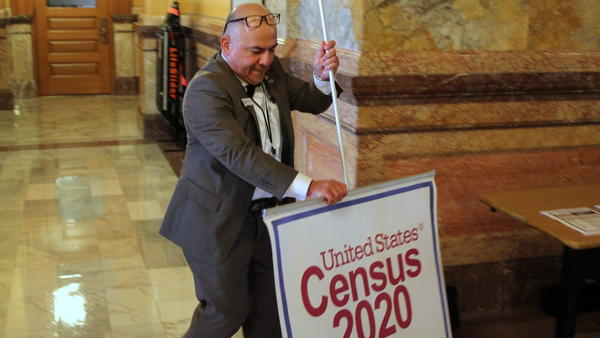 Carlos Urquilla-Diaz takes down a sign after a news conference at the Kansas Statehouse on Wednesday. He's a partnership specialist with the U.S. Census and is traveling the state to talk about the importance of the count.