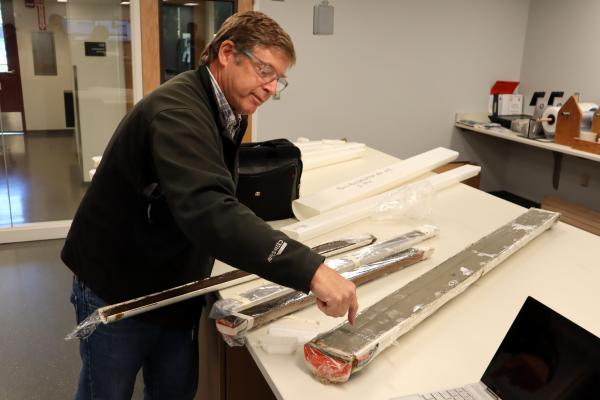 OSU marine geologist Chris Goldfinger shows an offshore sediment core, fat tube on right, and skinnier cores from Pacific Northwest lake bottoms, all of which contain traces of ancient earthquakes.