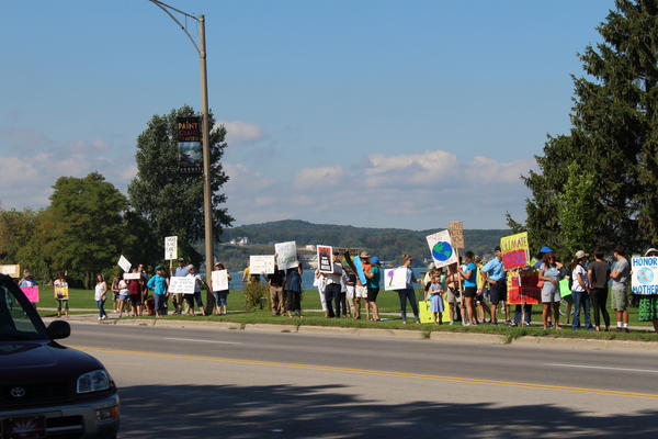 People in Traverse city lined up along a road to hold signs asking for action on climate change.