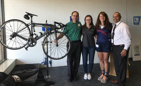 Green Mayor Gerald Neugebauer, Nora Anderson, triathlete Nancy Lyon-Stadler and CAK president and CEO Ren Camacho stand in front of the airport's new bike assembly station
