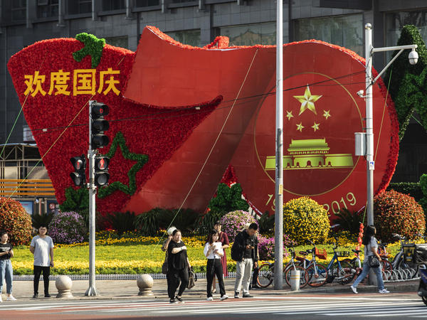 Pedestrians wait to cross a road in front of a floral installation celebrating the 70th anniversary of the People's Republic of China in Beijing. Streets have been cleaned and security increased before the Oct. 1 holiday.