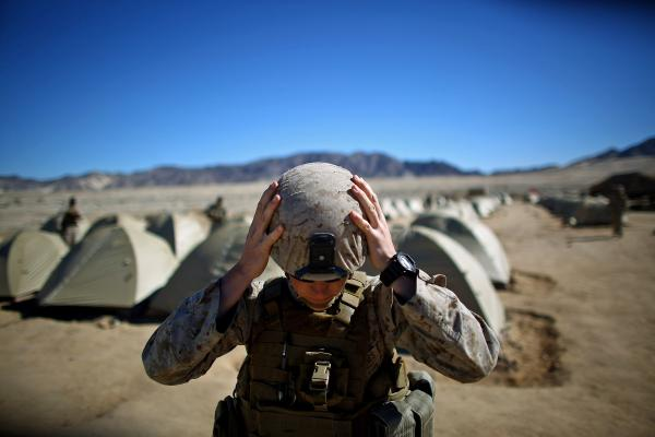 Sgt. Kelly Brown adjusts her helmet before a weapons check.