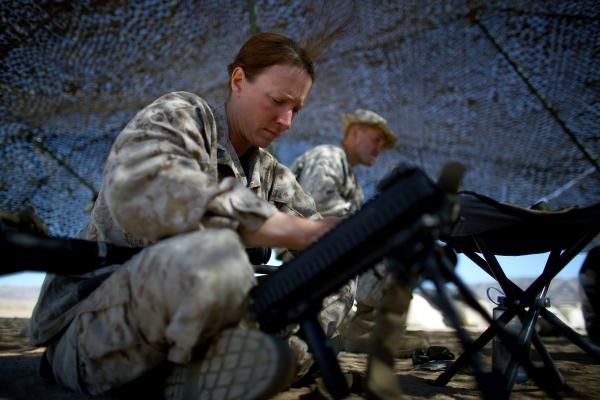 Brown, 30, cleans her weapon under the shade of camouflage netting at the Marine base at Twentynine Palms. Her grandfather's service in Korea and Vietnam inspired her to participate in this experiment.