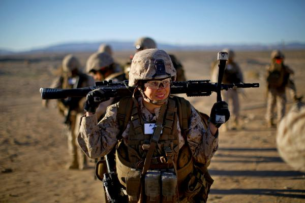 Sgt. Courtney White carries her machine gun before a live-fire exercise.