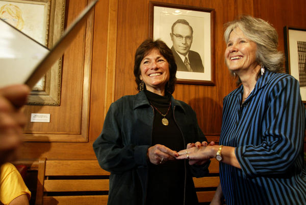 At Cambridge City Hall in Boston, Marcia Kadish (left) and Tanya McCloskey exchange rings as they are married before Clerk D. Margaret Drury on May 17, 2004. They were the first couple to be married in Cambridge that morning.