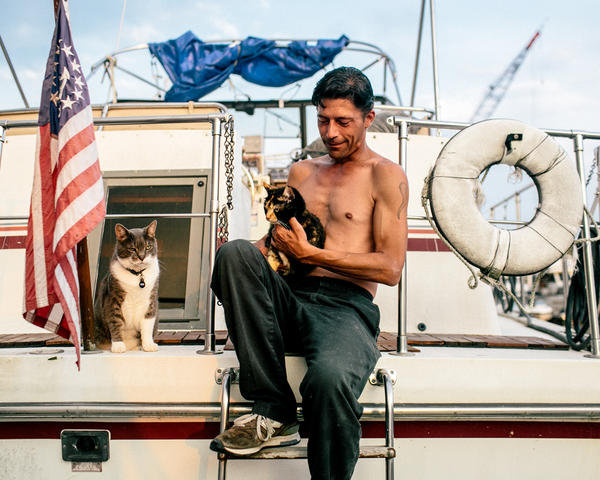 Paul Butler — with his cats, Nelson and Emma, aboard Spiritwood II<em> —</em> moved to Gangplank Marina in Washington, D.C., in 2007.