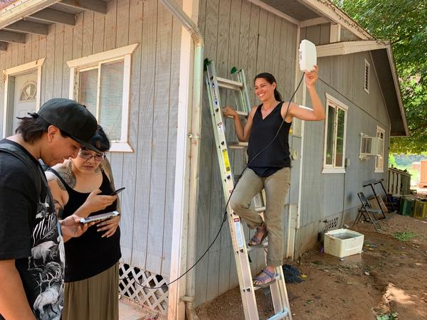 MuralNet CEO Mariel Triggs installs broadband equipment on the Havasupai reservation. Tribal members Travis Hamibreek and Ophelia Watahomigie-Corliss can see the Wi-Fi signal on their phones.