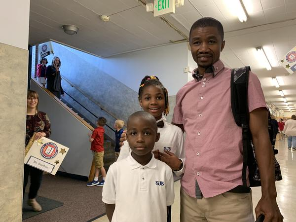 Elongo Gabriel, a refugee from the Democratic Republic of the Congo, drops his kids off on the first day of school at St. Joseph's Elementary in Missoula, Mont. He is one of 330 refugees to be resettled since 2016 in the college town of 75,000 people.