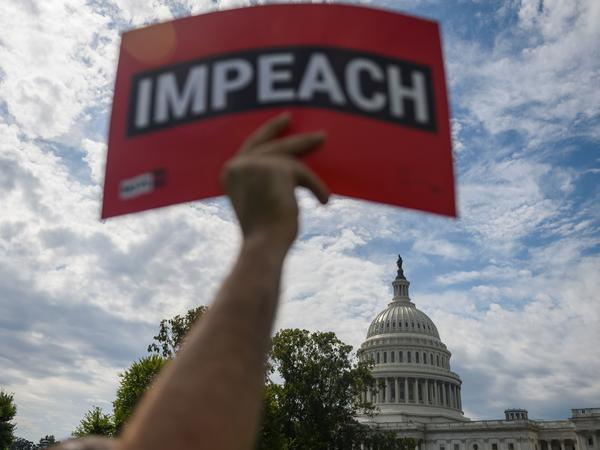 A protester holds up a sign in favor of impeachment outside the U.S. Capitol building on Thursday.