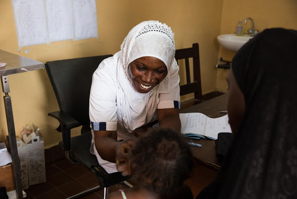 Nabia Drammeh, 27, a nurse, talks with Maram Ceesay, and her granddaughter, Awa at the Brufut Minor Health Center outside of Banjul, the Gambia. Awa's mother passed away during childbirth leaving her Maram to look after her. The 2-year-old is being treated for pneumonia.