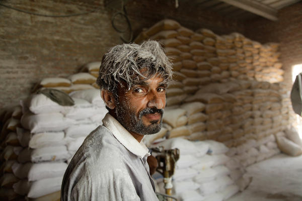 Malik Navid, a worker at a pink Himalayan salt mine in Khewra, Pakistan, waits for a large grinder to shoot out ground salt.