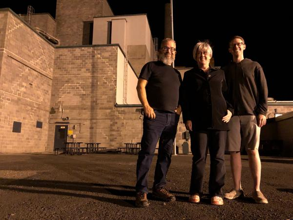 From left, Reg Unterseher, composer, Nancy Welliver, writer, and Mid-Columbia Mastersingers artistic director Justin Raffa in front of Hanford's B Reactor.