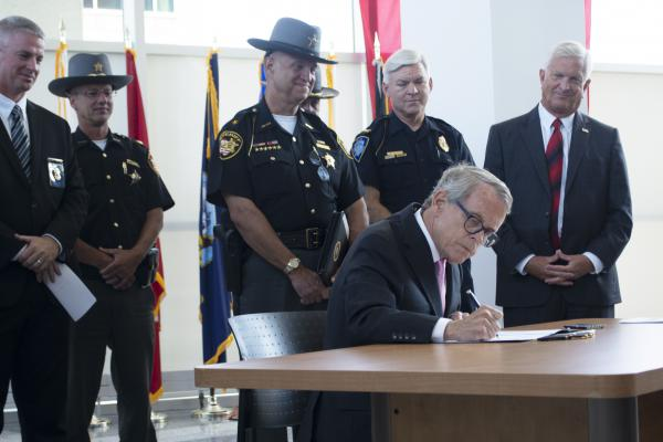 Gov. Mike DeWine signs an executive order creating the Ohio Narcotics Intelligence Center on July 31, 2019.