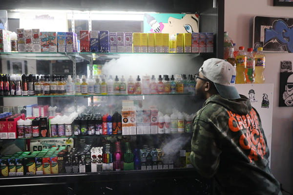 An employee vapes at a store in New York City.  Vaping, which many Americans have taken up as an alternative to smoking, has come under increased federal scrutiny following a rash of deaths related to the practice.