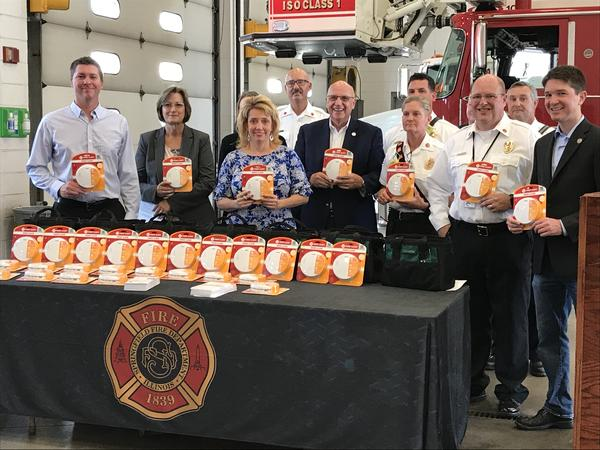 Fire safety officials and state lawmakers gather around a table of new model smoke detectors at a news conference in Springfield on Oct. 1
