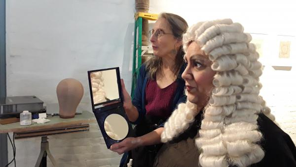 Luisa Torres, right, is transformed into a jowly old man in the hands of artist Beckie Kravetz.