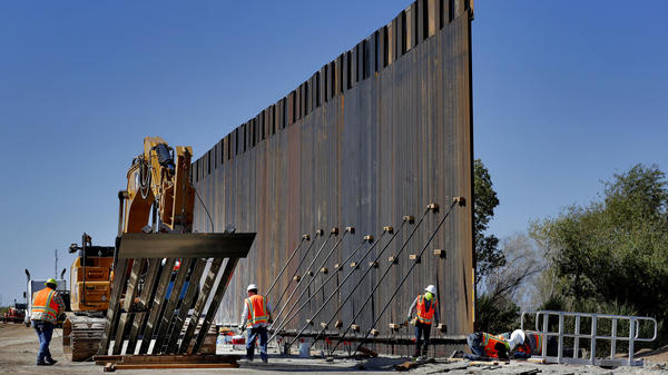 Government contractors erect a section of a Pentagon-funded border wall along the Colorado River in Yuma, Ariz., on Sept. 10.