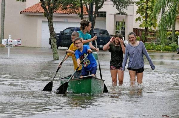William Potash paddles a canoe with friends through flooded streets in Davie in 2017.