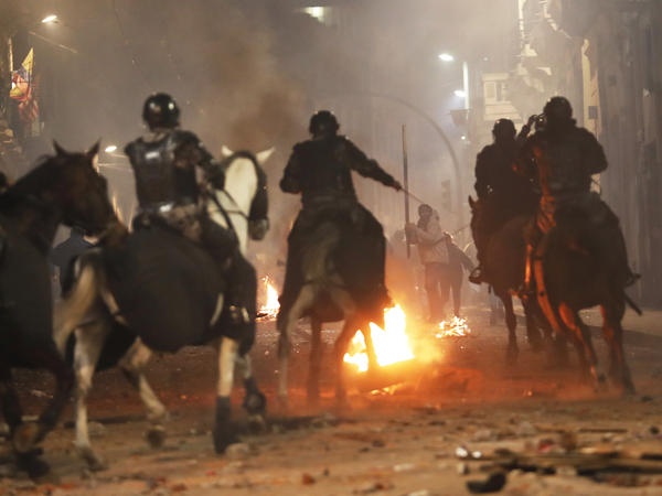 Mounted police in Quito advance on demonstrators protesting Ecuadorian President Lenín Moreno's move to scrap fuel subsidies, in a clash near the government palace late Thursday.