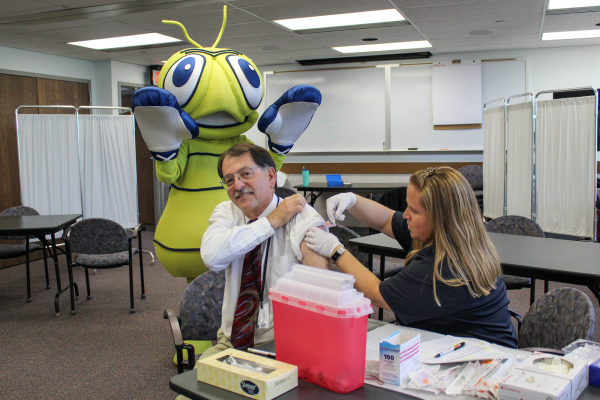 "The ""flu bug"" watches as Wyoming Department of Health Director Michael Ceballos receives his seasonal flu vaccine."