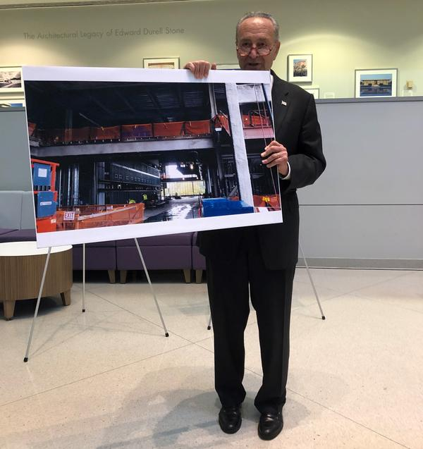 Sen. Chuck Schumer holds a photo of UAlbany's Emerging Technology and Entrepreneurship Complex under construction.