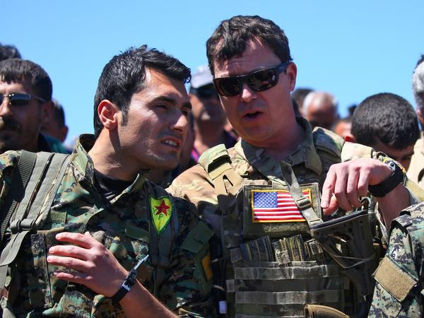 President Trump's plan for the Turkish-Syrian border contradicts recommendations from top officials in the Pentagon and the State Department. In this 2017 photo, a U.S. officer from the coalition against ISIS speaks with a fighter from the Kurdish People's Protection Units at the site of Turkish airstrikes near the northeastern Syrian Kurdish town of Derik.