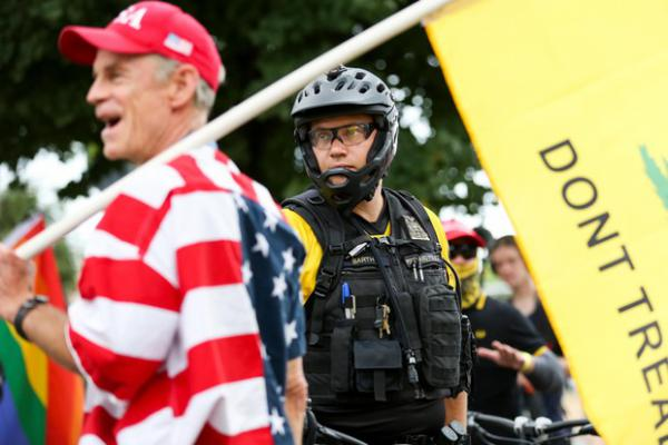 <p>Portland police watch as&nbsp;a Proud Boys rally continues under the Hawthorne Bridge in Portland, Ore., Saturday, Aug. 17, 2019. The Proud Boys espouse white supremacist ideology and have been&nbsp;designated&nbsp;a hate group by the Southern Poverty Law Center.</p>