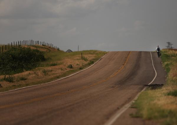 "A man hitchhikes down a lonely stretch of highway in Stockton, Kansas. When rural America was chronicled 50 years ago by Jack Kerouac in his autobiographical novel ""On the Road"", it was an America full of promise and economic potential, where the majestic openness of the land was entwined with the cult of the automobile. Today, partly due to the loss of the independent family farm, rural America is a state of economic and demographic decline."