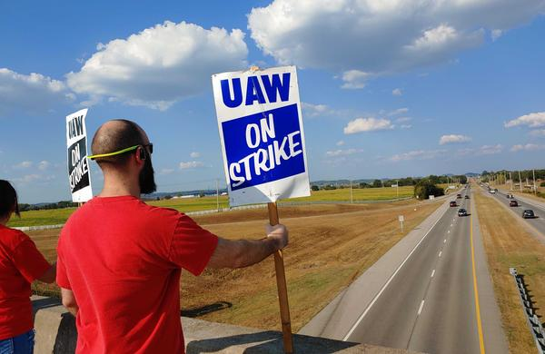 United Auto Workers members hold signs outside General Motors' Spring Hill plant as part of a nationwide strike that started on Sept. 14.