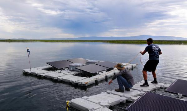 <p>OIT renewable energy students Ian Riley (left) and Juan Billarreal maneuver a solar powered lake aerator on Upper Klamath Lake.</p>