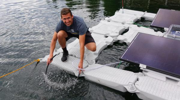 <p>Oregon Institute of Technology student Juan Billarreal holds the aeration hose that will add dissolved oxygen to Upper Klamath Lake.&nbsp;</p>