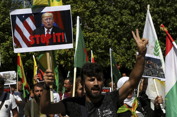 A Kurd living in Cyprus shouts slogans in front of the U.S. Embassy in Nicosia, Cyprus, on Thursday to protest Turkey's offensive into Syria. The protesters chanted slogans condemning Turkey's military action and urging the withdrawal of Turkish forces.