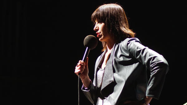 Ophira Eisenberg performs on stage on <em>Ask Me Another</em> at Cullen Performance Hall at the University of Houston, in Houston, Texas.