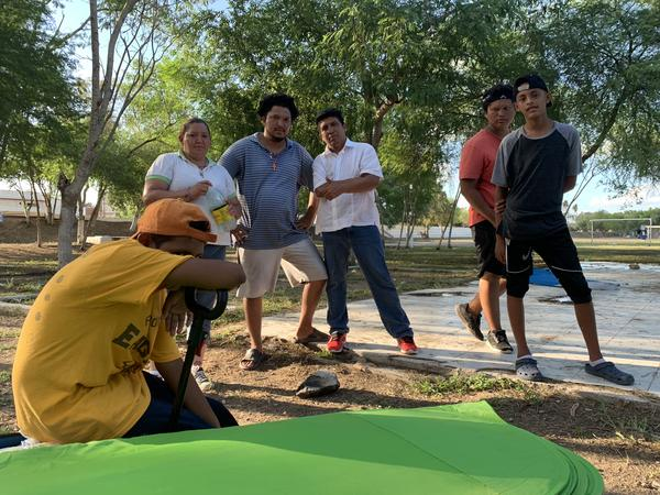 A group of asylum seekers in a small park in Matamoros, Mexico, where the shower tents and clean water are available.