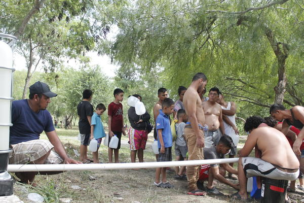 People stand in line for clean water.