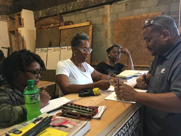 Students in the tool library's home-building class talk strategy before tackling a project.