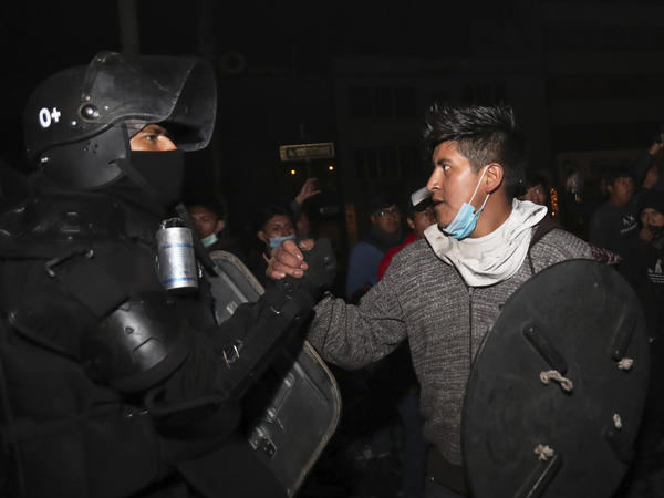 A protester shakes hands with a security officer in Quito, Ecuador, on Sunday as they celebrate the government's announcement that it has cancelled an austerity package. The package had triggered violent protests that paralyzed the economy and left seven people dead.