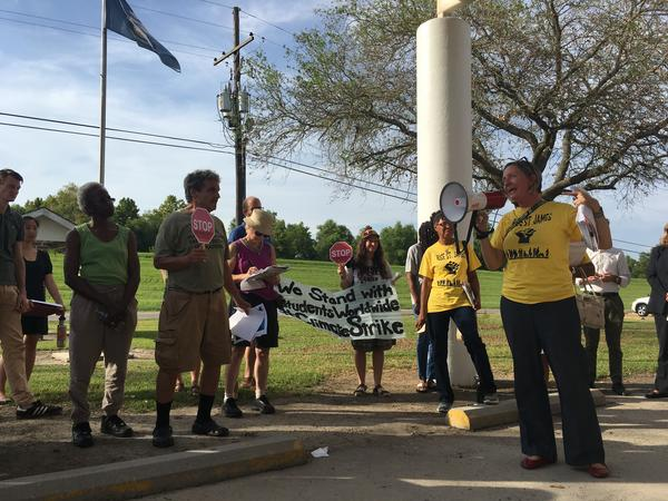Anne Rolfes, with the Louisiana Bucket Brigade, leads a crowd in a protest chant prior to a public meeting in Vacherie, LA related to the proposed Formosa chemical plant. Residents in the region have been protesting against industry for years.