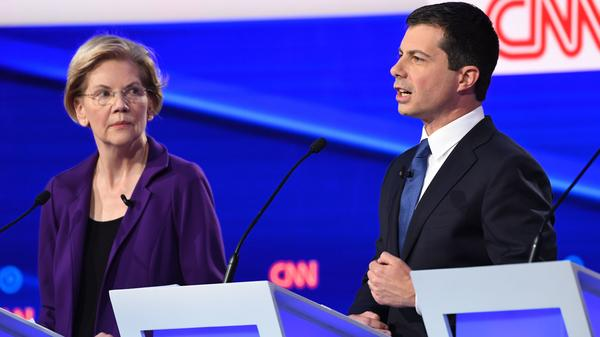 Massachusetts Sen. Elizabeth Warren looks on as South Bend, Ind., Mayor Pete Buttigieg speaks during Tuesday's Democratic presidential debate. Warren's policy positions were described as unrealistic and expensive by her rivals in the Democratic debate.