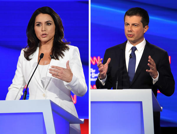 Hawaii Rep. Tulsi Gabbard and South Bend, Ind., Mayor Pete Buttigieg answer questions during Tuesday night's debate in Ohio. The two military veterans each took a very different tack when it came to the latest foreign policy crisis over Syria and Turkey.