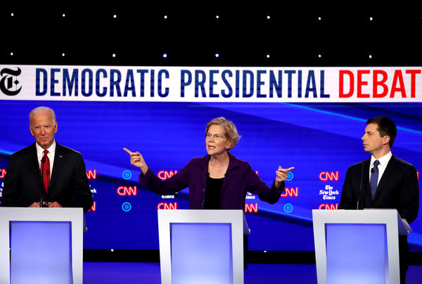 Left to right: former Vice President Joe Biden, Massuchusetts Sen. Elizabeth Warren and South Bend, Ind., Mayor Pete Buttigieg react on stage during the Democratic presidential debate at Otterbein University.
