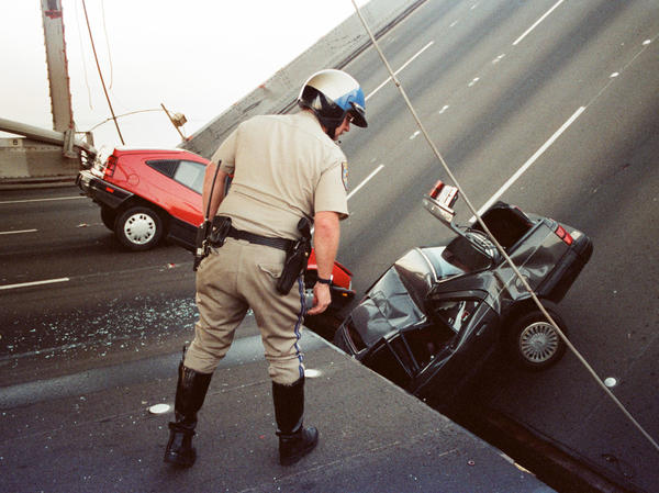 A California Highway Patrol officer checks cars that fell when the upper deck of the San Francisco Bay Bridge collapsed onto the lower deck after the 1989 Loma Prieta earthquake.