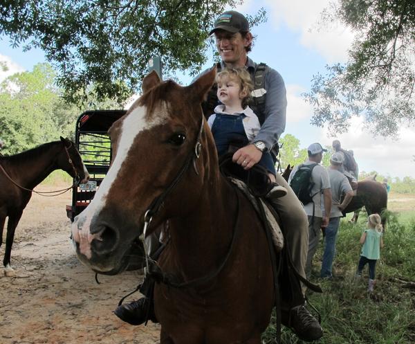 Carlton Ward Jr. cradles his son, Carlton III, before taking off on horseback from Highlands Hammock State Park